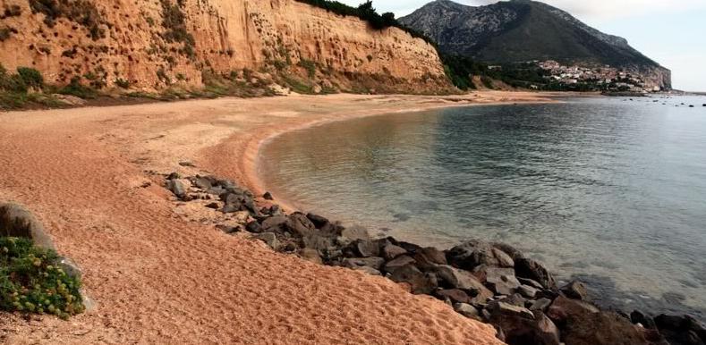 Spiaggia di Sos Dorroles abbracciata da rocce arancioni
